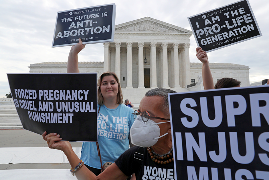 Hannah Wolfe, left, protests against abortion rights as Laurie Arbeiter protests for abortion rights in front of Wolfe, outside of the U.S. Supreme Court building in Washington, D.C.