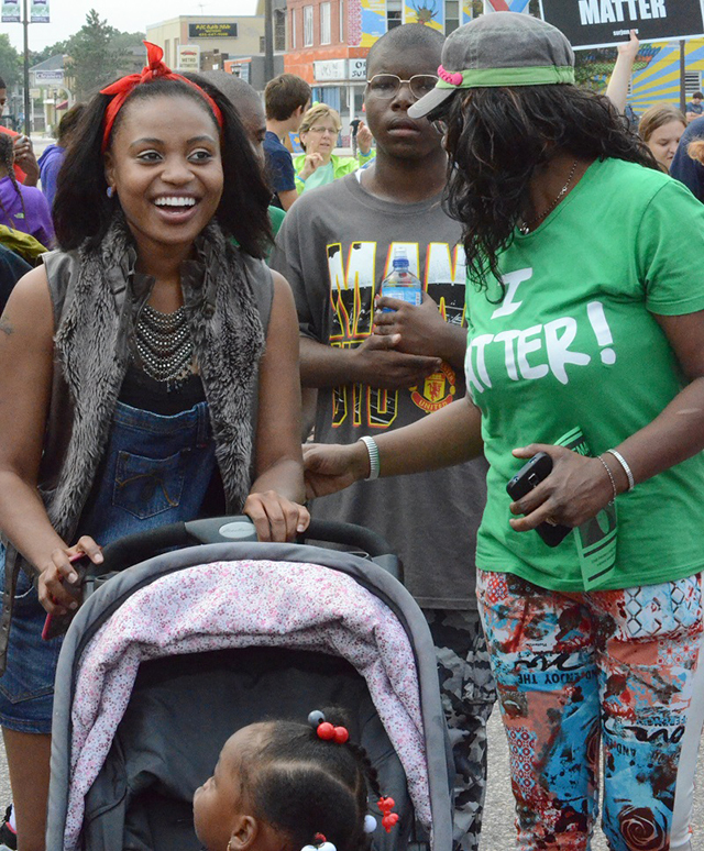 Ferneatress pushes her daughter Armery in a stroller down Snelling Avenue.