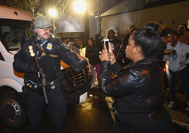 A Minneapolis police officer tells a women to back up