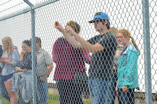 Fairgoers watch the protest from the other side of the fence.