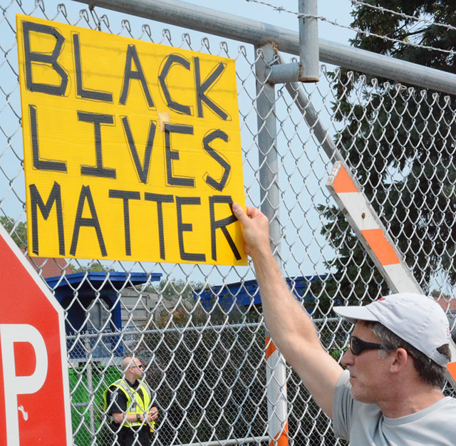 Another protester holds up a sign against the closed gate.