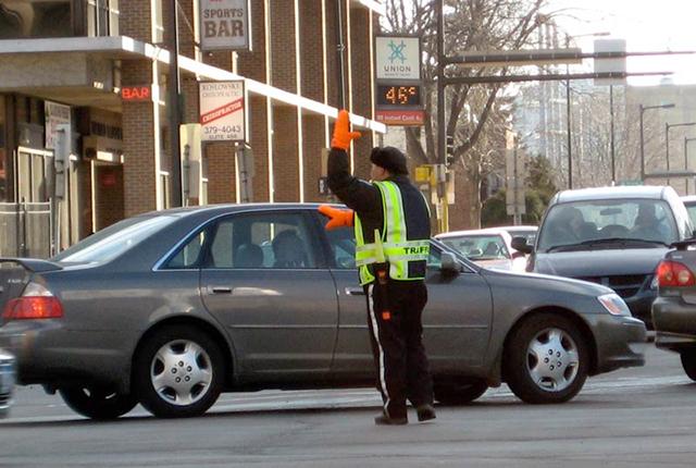 A traffic cop directing detoured traffic through Northeast Minneapolis
