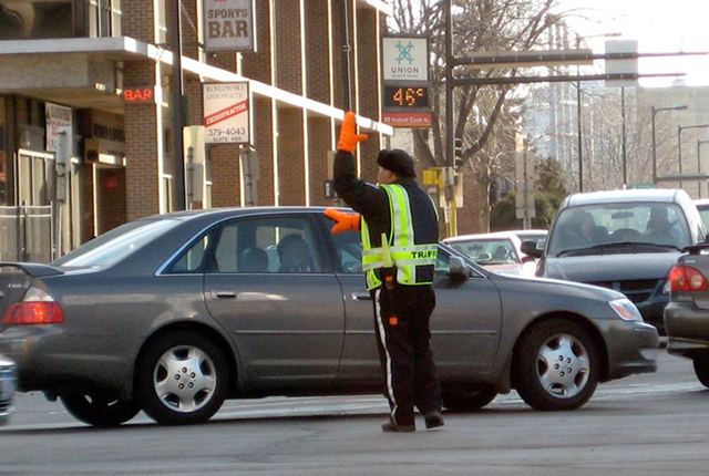 A traffic cop directing detoured traffic through Northeast Minneapolis