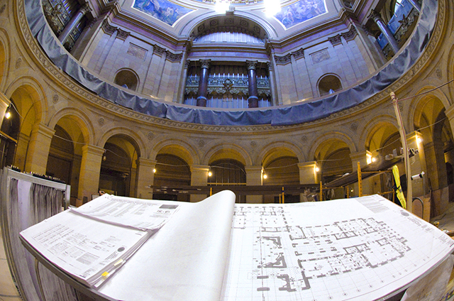 Architectural drawing are displayed on a bench in the rotunda