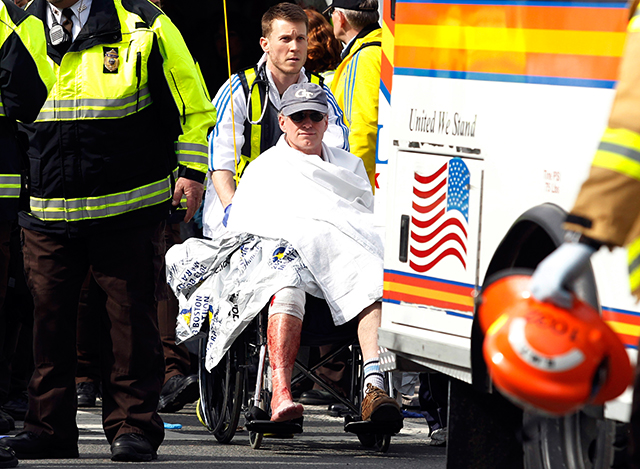 A runner in a wheelchair is taken from a triage tent