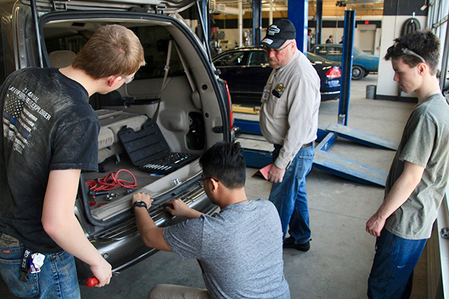 Students removing a bumper in Russ Tesmer's auto body repair class