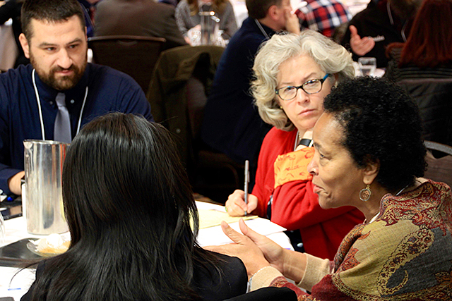 A group of attendees discussing the issue of equity in charter schools