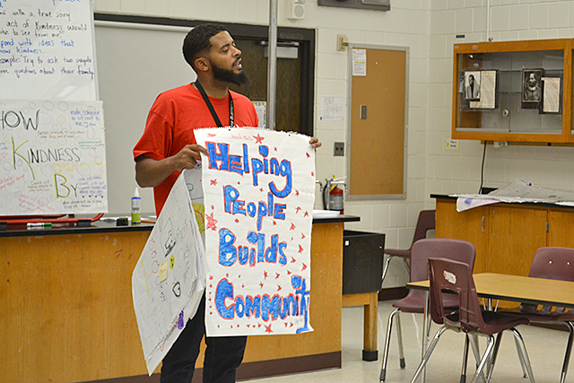Chris Pierce holding up a student-made sign