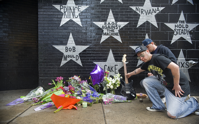 Christopher LaCroix, of Minneapolis, leaves a guitar at a memorial under the Pri
