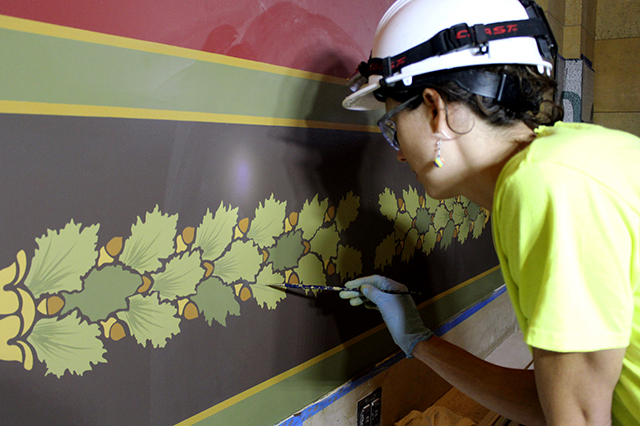 Emily Litjens adding detail to an oak leaf swag in a main corridor of the East W