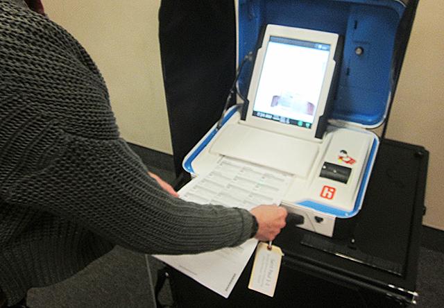 An election volunteer feeding a ballot into a voting machine