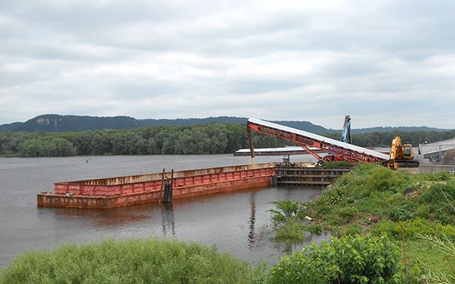 Frac sand being loaded onto a barge on the Mississippi River in Winona.