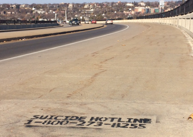 A suicide hotline number painted onto St. Paul's High Bridge.