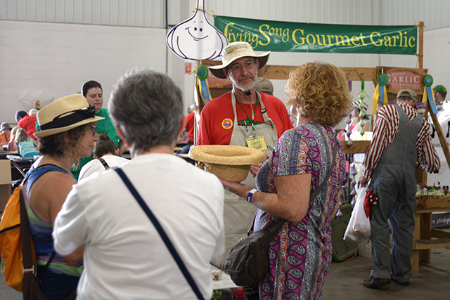 Jerry Ford talking to customers next to his Living Song Farm booth.