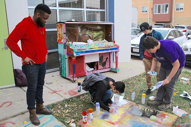 Ninth-grader Jesus Castillo Palacios, center, working on a piece of graffiti