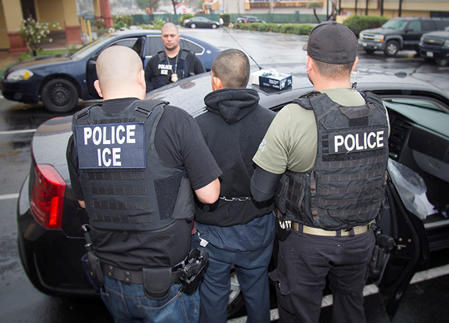 Immigration and Customs Enforcement officers detaining a suspect