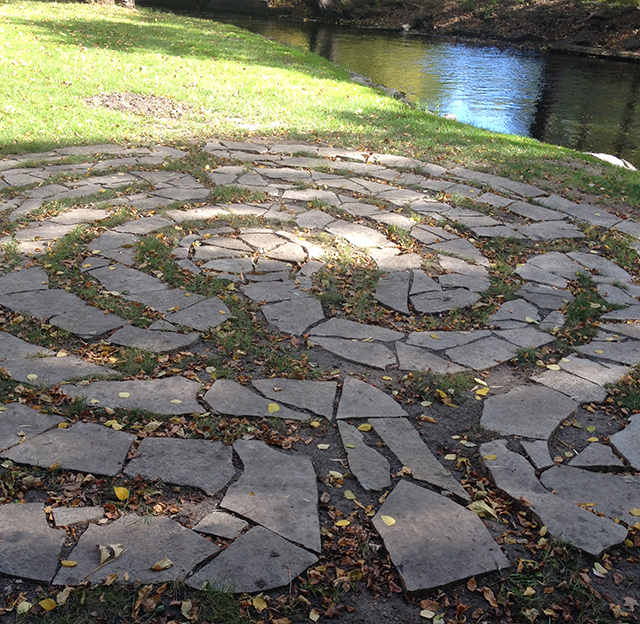 A stone labyrinth built into the ground right in view of the creek.
