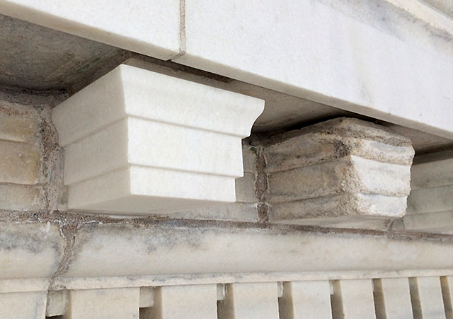 A new modillion block of marble next to a deteriorated one.