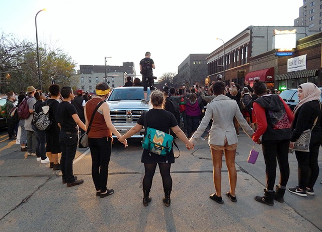 Organizers ask marchers to join hands in solidarity.