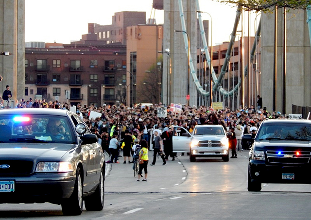 Minneapolis police officers clear the path as marchers trek into NE Mpls