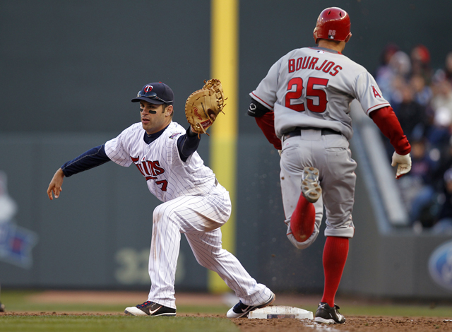 Joe Mauer catching a throw to first base on a ball hit by Peter Bourjos during the ninth inning.