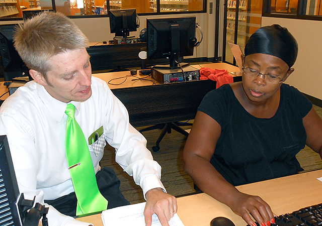 Instructor Mike Reis teaches Grace Mwamasika at a free computer software class at Burnsville's Burnhaven Library.