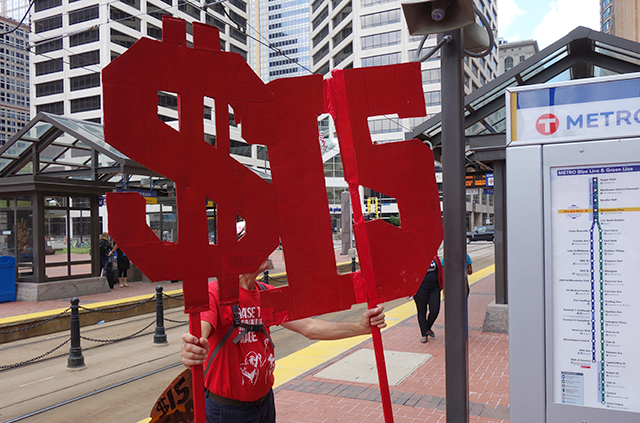 """Supporter of the minimum wage charter holding """"5"""" signs at the Thursday rally."""