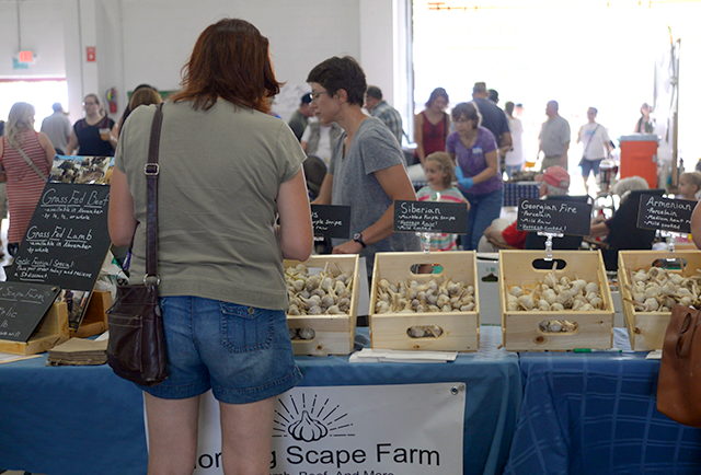Customers shopping for garlic at the Morning Scape Farm booth