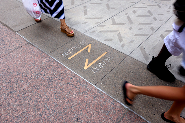Sidewalk inlays attempt to direct pedestrians to skyway entrances.