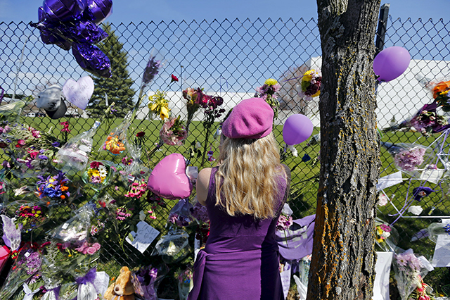 Cami Ponzio looking at flowers and balloons placed in tribute to Prince at a mak