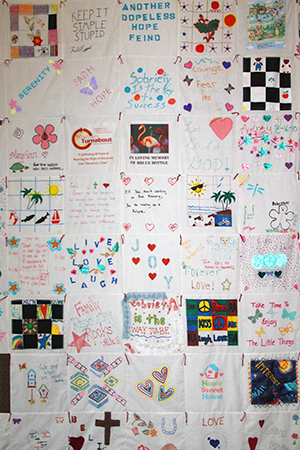 A quilt sewn by Project Turnabout clients hangs in the meditation room.