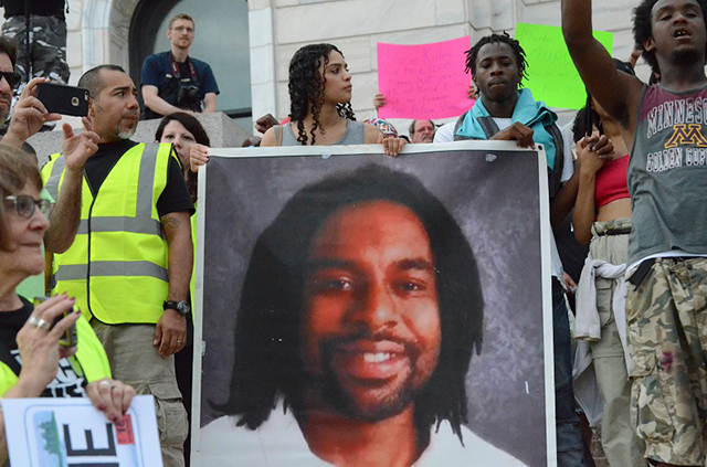 Protesters holding a large photo of Philando Castile.