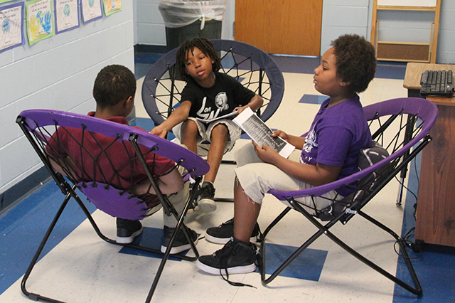 """LoveWorks students practicing a song from """"Hamilton"""" in trampoline chairs."""