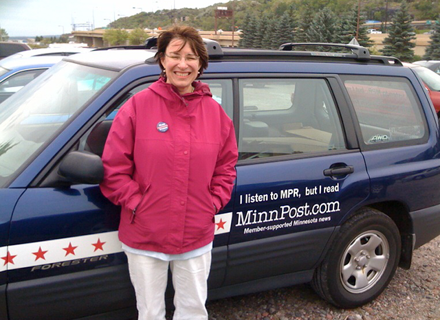 Sen. Amy Klobuchar posing next to one of MinnPost's mobile promo units