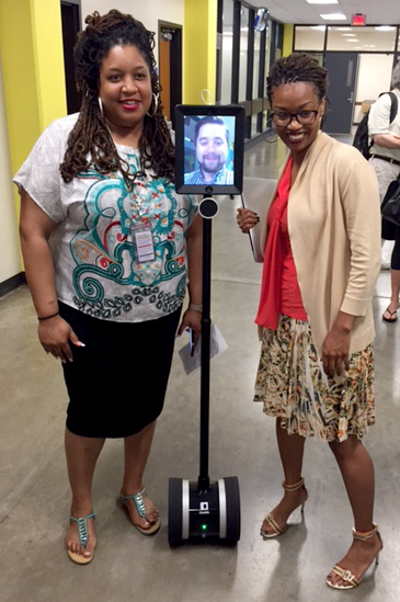 Lanise Block, left, and Makisha Boothe, right, posing with a telepresence robot