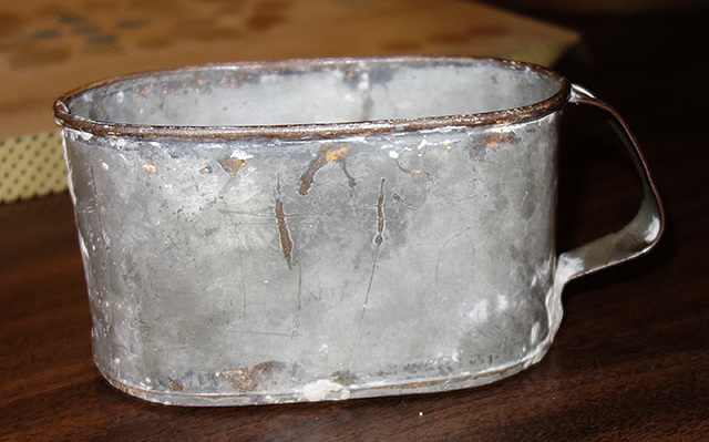 A metal cup once used by inmates in the jail