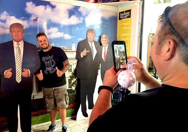 A fair-goer posing with a cutout of Donald Trump