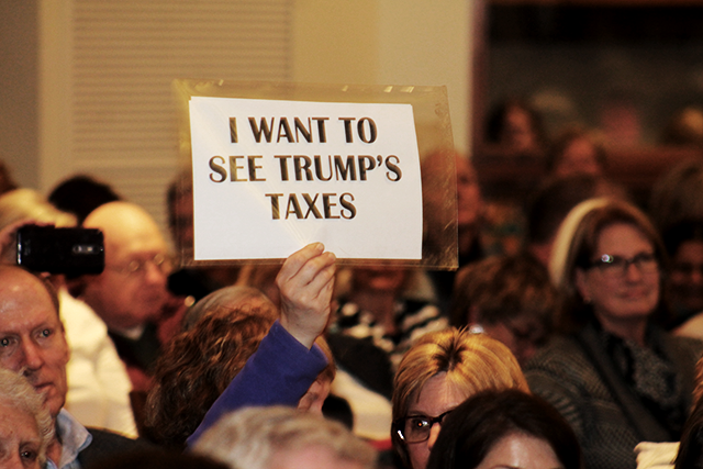 A town hall attendee holding up a sign