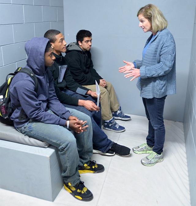 Wisdom volunteer Jane Miller, right, talks with students