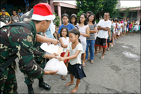 A soldier distributes relief to villagers during a gift-giving event at the evacuation center in San Roque, Albay province, south of Manila on Tuesday.