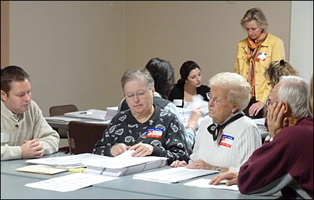 Two elections judges in Shakopee are shown flanked by each campaign's observers.