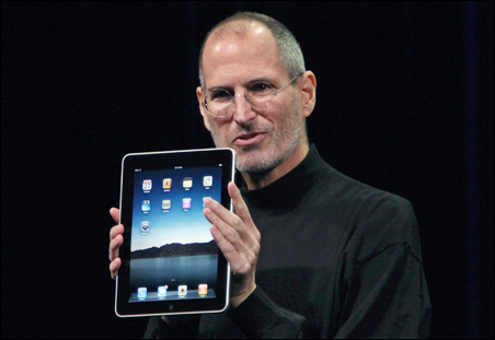 "Apple CEO Steve Jobs holds the new ""iPad"" during the launch of Apple's new tablet computing device on Wednesday."