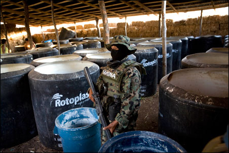 A Marine stands next to ingredients of crystal methamphetamines at a clandestine laboratory discovered by the police and military in the municipality of Badiraguato, in the Mexican state of Sinaloa, June 12, 2009.