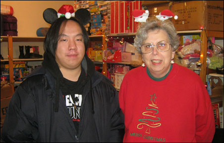 Standing in front of gifts they'll help distribute to refugees and immigrants through MORE are volunteers Sou Vang, left, and Diane Phillippi.