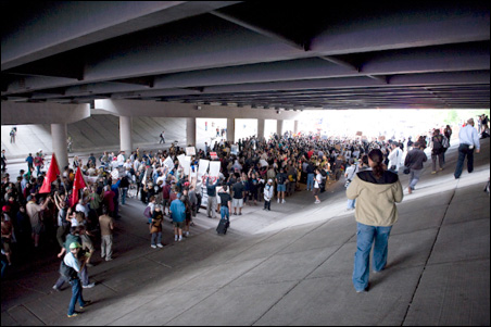 Marchers pass under the I-35E bridge.