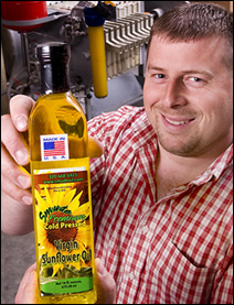 Tom Smude displays a bottle of Smude Farms cold-pressed sunflower oil