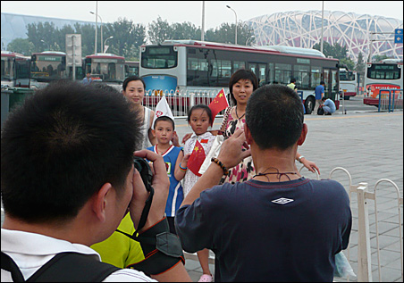 Families eagerly line up at the Olympics' signature sites to snap keepsake photos.