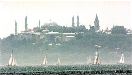 Sailing yachts cruise through Bosphorus waterways past Istanbul's Topkapi Palace.