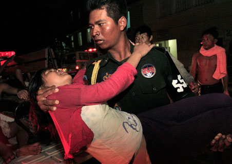 A stampede victim is carried to safety in Phnom Penh on Tuesday.