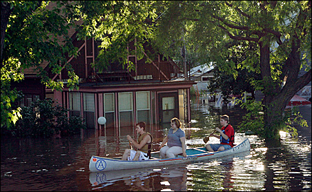 Residents ride down a flooded street to their home to rescue their cat in Cedar Rapids, Iowa, last week.